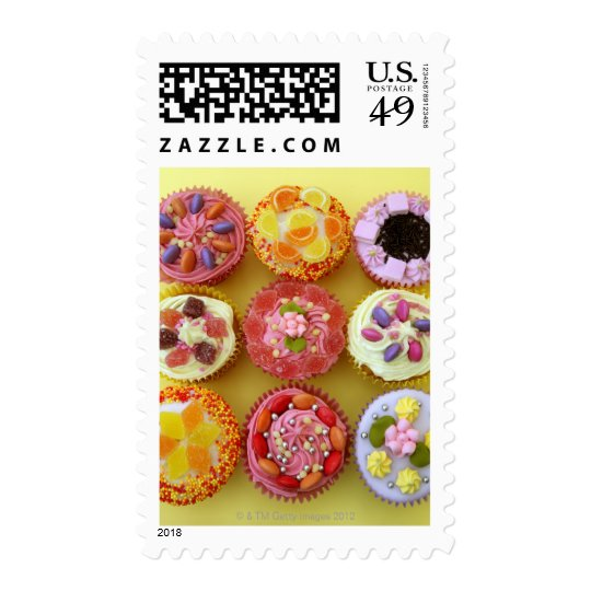 Nine cupcakes each decorated with candy in a postage