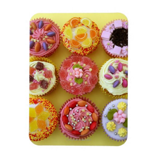 Nine cupcakes each decorated with candy in a rectangular magnet