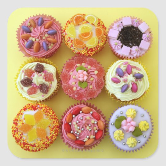 Nine cupcakes each decorated with candy in a square sticker