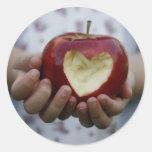 Niño con el corazón de la manzana pegatina redonda