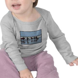 Niño de la muchedumbre que practica surf camisetas