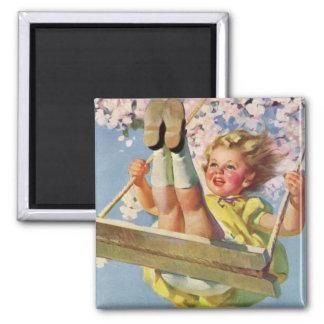 Niño del vintage, chica que balancea en el imanes para frigoríficos
