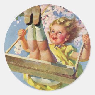 Niño del vintage chica que balancea en el oscilac etiqueta