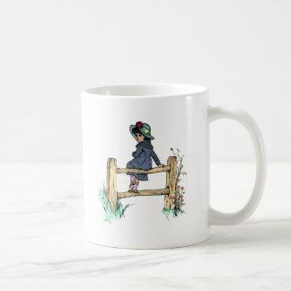Niño joven en un impermeable taza