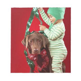 Niño pequeño que adorna un perro libretas para notas