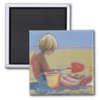 Niño pequeño que juega en la arena con una pala imán de nevera