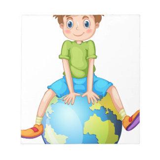 Niño pequeño que se sienta en el planeta azul libretas para notas