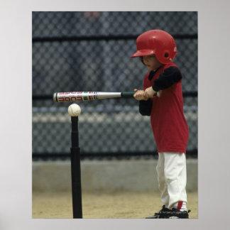 Niño que golpea una bola de la camiseta posters