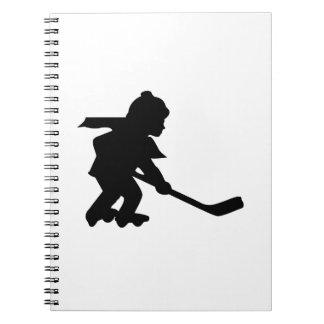 Niño que juega a hockey del rodillo cuadernos