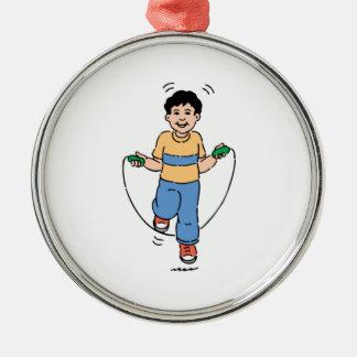 Niño que juega con una comba adorno redondo plateado