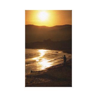 Niño que juega en una playa en la puesta del sol impresión en lona estirada