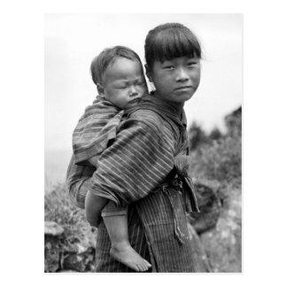 Niño que lleva del chica asiático en ella detrás postales