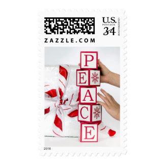 Niño que pone encima de bloques del alfabeto sellos postales