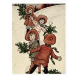 Niños con las bolas de nieve que lanzan del acebo postal