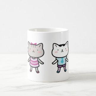 Niños del gatito al lado de uno a tazas