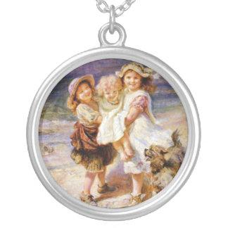 Niños del vintage en la playa collar plateado