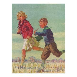 Niños del vintage que corren a los libros que llev tarjetas postales