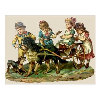 Niños del vintage y carro de perro postal