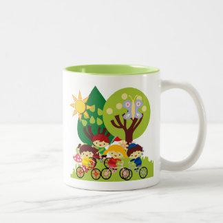 Niños en las bicis taza de café