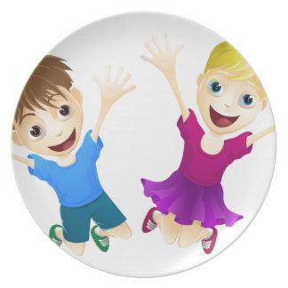 Niños felices que saltan en el aire plato