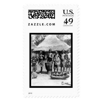 Niños por una casa de tejado cubierto con paja en sello