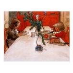 Niños que comen cena postal