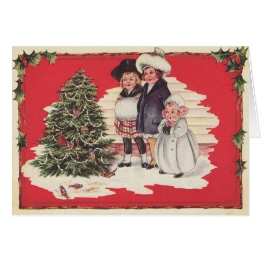 Niños que gozan del árbol de navidad felicitacion