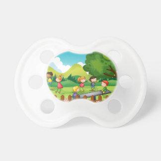 Niños que juegan en el campo chupetes de bebe