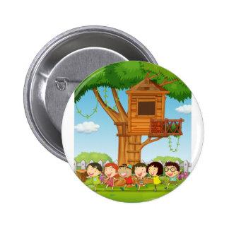 Niños que juegan en el jardín pin redondo de 2 pulgadas