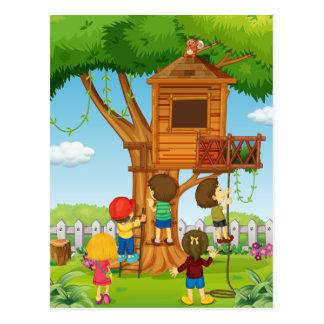 Niños que juegan en la casa del árbol tarjeta postal