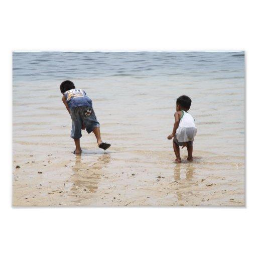 Niños que juegan en la playa fotografías