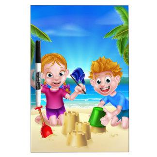 Niños que juegan en la playa pizarra blanca