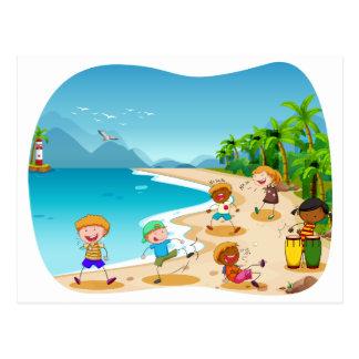 Niños que juegan en la playa postal