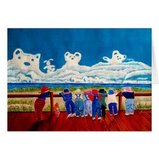Niños que juegan en la playa y las nubes de tarjeta pequeña