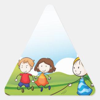 Niños que juegan la cuerda de salto pegatina triangular