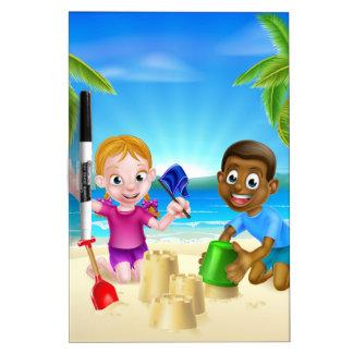 Niños que juegan por el mar pizarras blancas de calidad