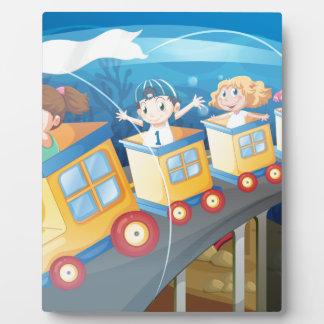 Niños que montan en el tren en el túnel placa