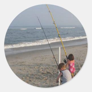 Niños que pescan en la playa pegatina redonda