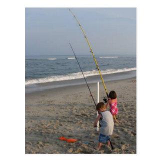 Niños que pescan en la playa postales