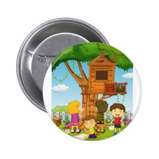 Niños que pintan la casa del árbol en el parque pin redondo de 2 pulgadas