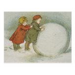 Niños que ruedan bolas de nieve postal
