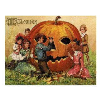 Niños que tallan la calabaza de la linterna de tarjetas postales