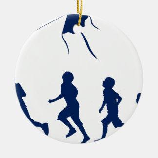 Niños que vuelan una cometa adorno navideño redondo de cerámica