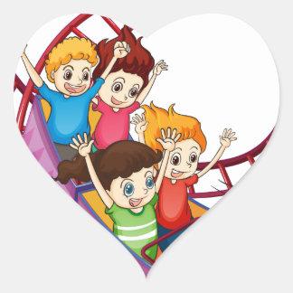 Niños valientes que montan en un paseo de la pegatina en forma de corazón