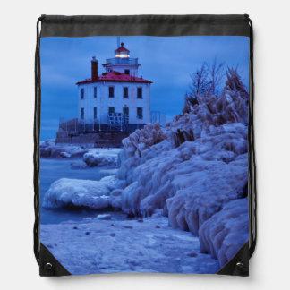Noche hivernal, helada en el faro del puerto de mochilas