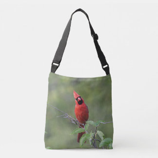 Northern cardinal stands on a tree branch crossbody bag