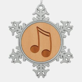 Nota de la música grabada en el diseño de madera adorno de peltre en forma de copo de nieve