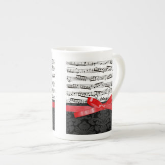 Notas de la música y falsa cinta roja taza de té