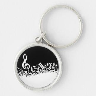 Notas musicales embarulladas blancas sobre negro llavero redondo plateado