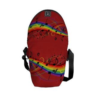 Notas musicales negras del arco iris sobre rojo bolsa messenger
